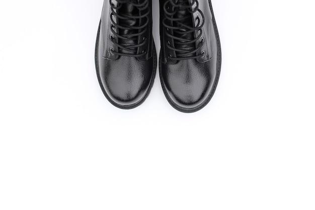 Czarne skórzane buty na białej powierzchni. modne nowoczesne buty damskie w stylu militarnym.