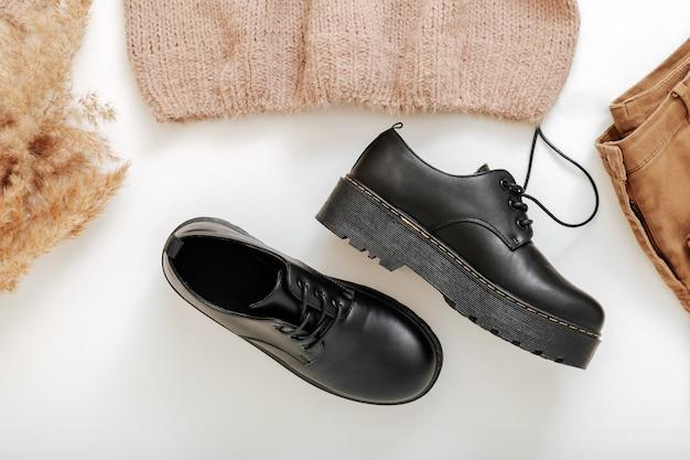 Czarne skórzane buty na białym. wiosenno-jesienny strój na płaskim obcasie z modnymi, casualowymi, czarnymi sznurowanymi butami ze sztucznej skóry na grubych gumowych podeszwach. para stylowe buty unisex dla kobiet i mężczyzn. latające buty widok z góry