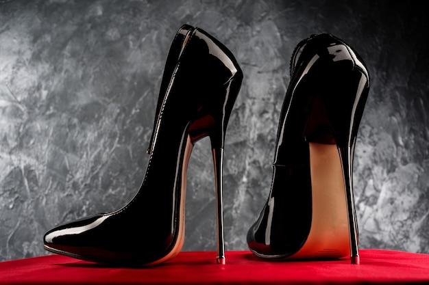 Czarne skórzane szpilki na szpilce z paskiem przy kostce na czerwonej satynie