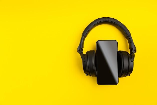 Czarne słuchawki bezprzewodowe i pusty ekran smartfona na jasnym żółtym tle kolorowe