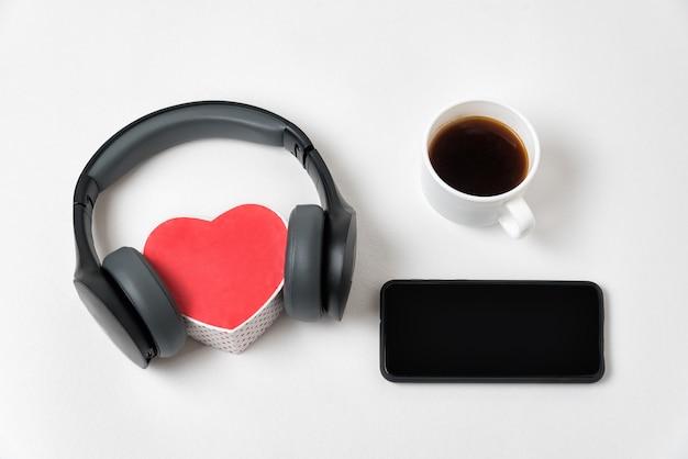 Czarne słuchawki i pudełko w kształcie serca, smartfon i filiżanka kawy. białe tło