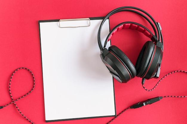 Czarne słuchawki i schowek z białym czystym papierem. koncepcja słuchania materiału audio