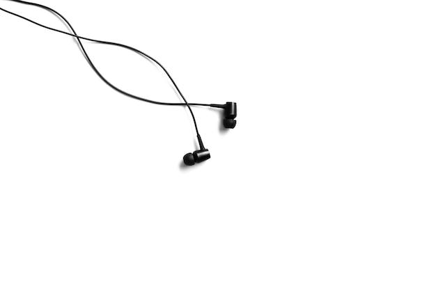 Czarne słuchawki leżące na białym tle. koncepcja muzyki współczesnej. technologia audio.