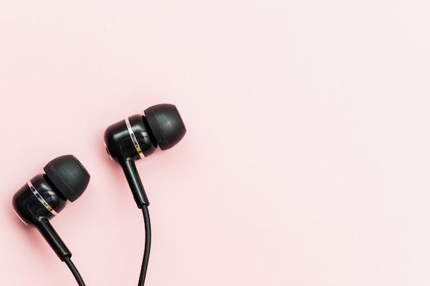 Czarne słuchawki na różowym tle do koncepcji słuchania dźwięku