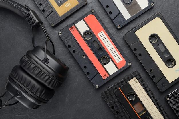 Czarne słuchawki nauszne i kompaktowe kasety z taśmą audio na łupku