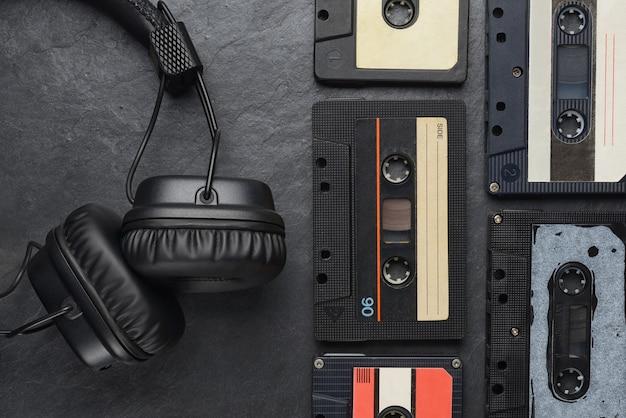 Czarne słuchawki nauszne i kompaktowe kasety z taśmą audio