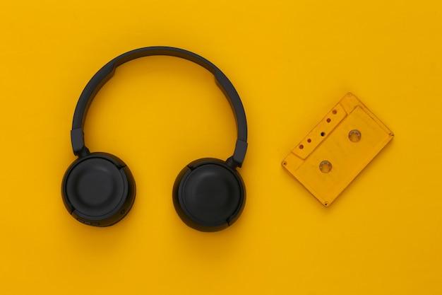 Czarne słuchawki stereo z kasetą audio retro na żółto