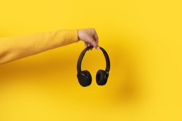 Czarne słuchawki w ręku na żółtym tle