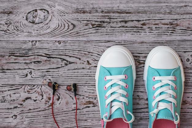 Czarne słuchawki z czerwonym przewodem i turkusowe trampki na drewnianej podłodze. styl sportowy. leżał na płasko. widok z góry.