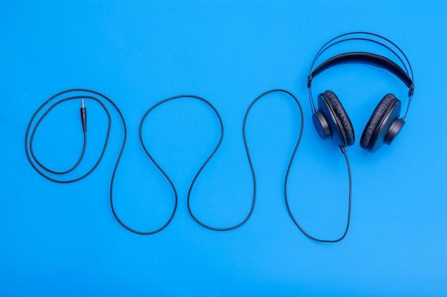 Czarne słuchawki z przewodem w kształcie fali na niebieskim tle. akcesoria do słuchania muzyki i komunikacji.