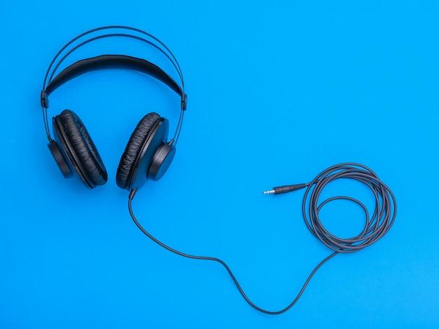 Czarne słuchawki ze zwiniętym przewodem na niebieskim tle.