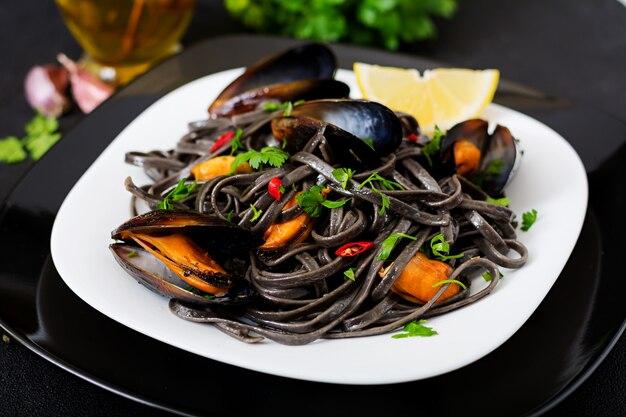 Czarne spaghetti. czarny makaron z owocami morza z małżami na czarnym stole. przysmaki kuchni śródziemnomorskiej