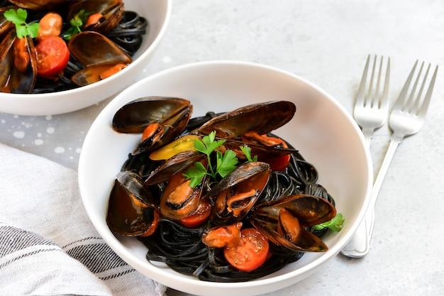 Czarne spaghetti. czarny makaron z owocami morza z małżami.