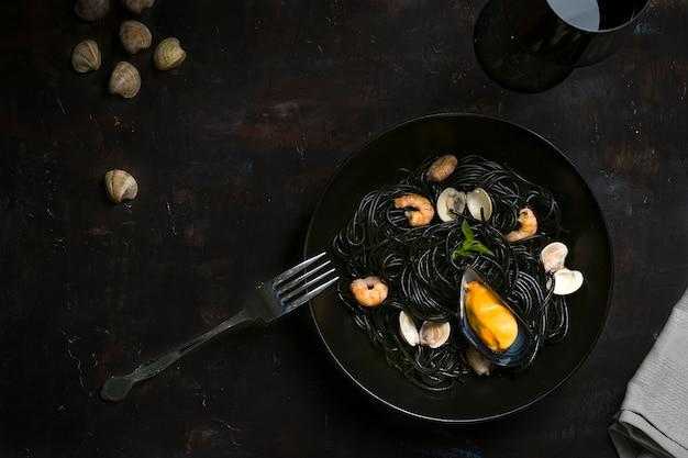Czarne spaghetti z małżami, małżami i krewetkami na ciemnym stole