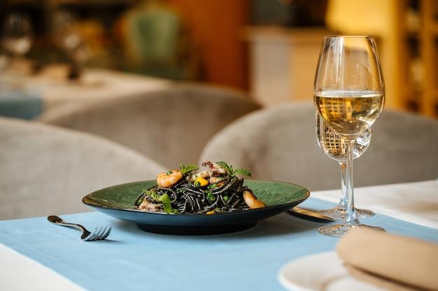 Czarne spaghetti z owocami morza i sosem szafranowym z białym winem