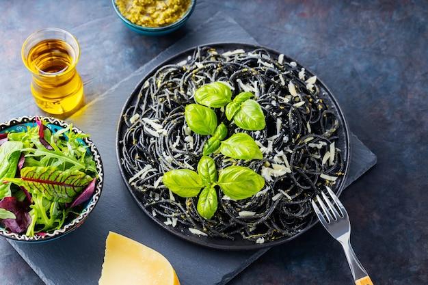 Czarne spaghetti z tuszem mątwy na ciemnym tle. makaron z tartym serem i świeżą zieleniną