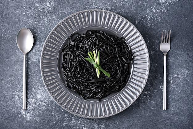 Czarne spaghetti z tuszem mątwy na szarym talerzu z łyżką i widelcem na szarym tle, czas jeść koncepcja