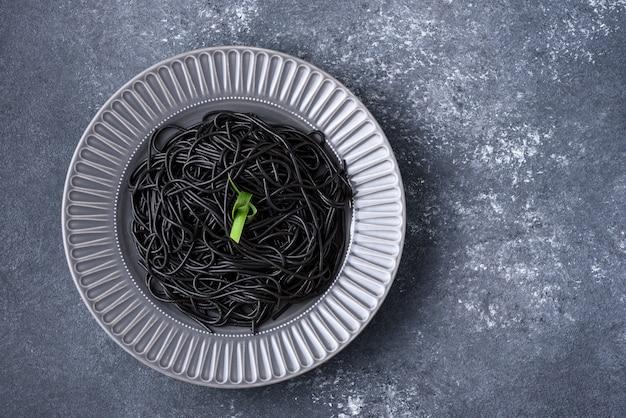 Czarne spaghetti z tuszem mątwy z zielonym liściem na szarym talerzu na szarym tle z miejscem na kopię, koncepcja czarnego makaronu