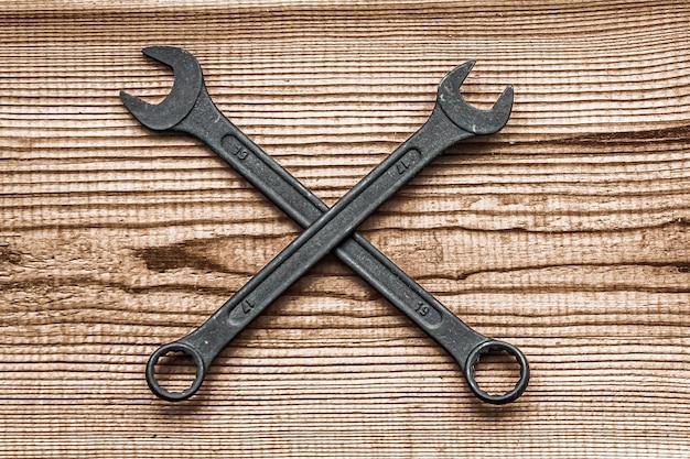 Czarne stalowe klucze leżą w układzie poprzecznym na ciemnobrązowym tle z teksturą drewna