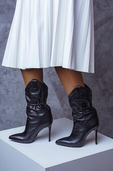 Czarne stylowe buty i biała bluzka na ciemnym tle