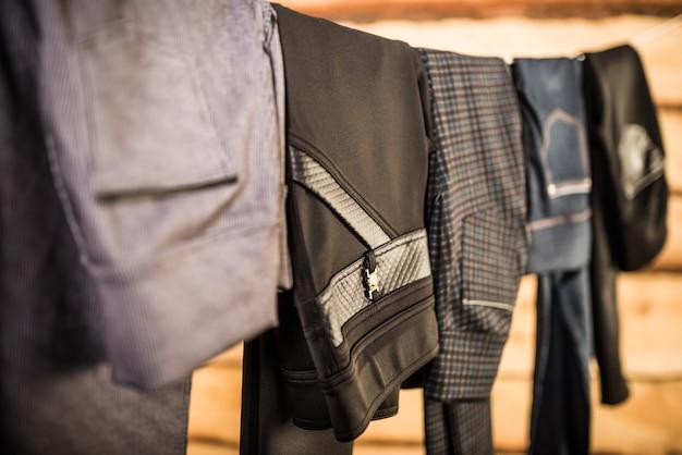 Czarne stylowe damskie spodnie i dżinsy wiszą na sznurku w szafie.