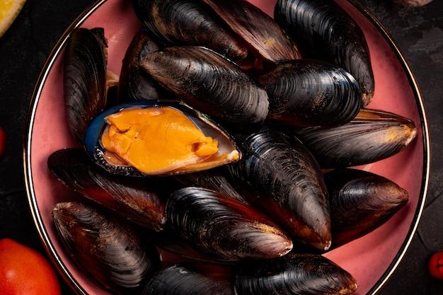 Czarne surowe małże na talerzu z bliska