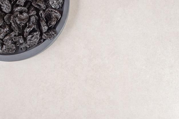 Czarne suszone śliwki na drewnianym talerzu.