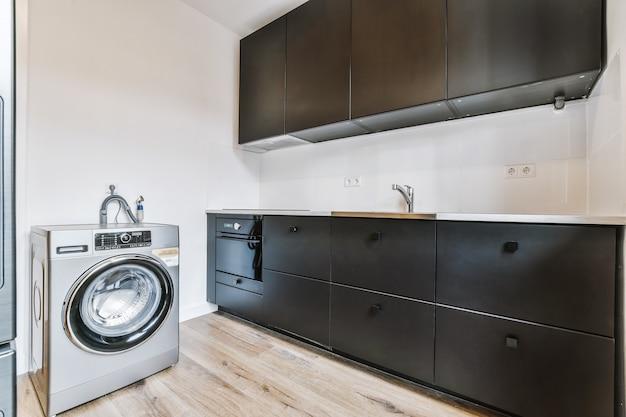 Czarne szafki z kuchenką i zlewozmywakiem zlokalizowane w pobliżu współczesnej pralki w kuchni apartamentu