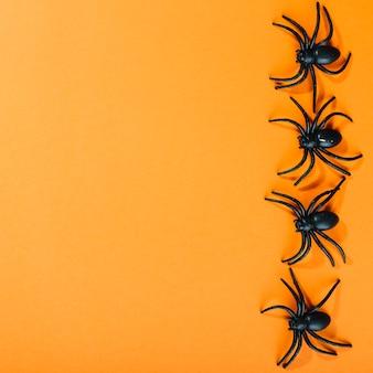 Czarne sztuczne pająki układane w szeregu