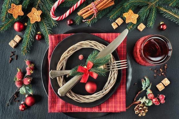 Czarne talerze i zabytkowe sztućce z dekoracjami świątecznymi w kolorze zielonym, czerwonym i pomarańczowym
