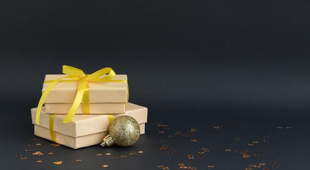 Czarne tło boże narodzenie z pudełkami prezentowymi i ozdobami świątecznymi