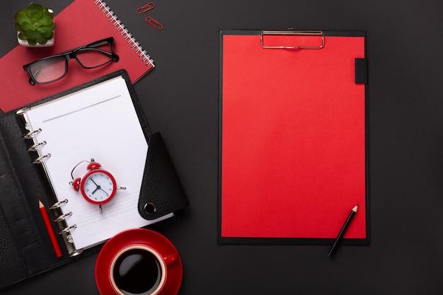 Czarne tło czerwony kubek kawy notatnik budzik kwiat dziennik wyniki klawiatury na stole. widok z góry z miejsca na kopię