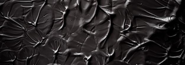 Czarne tło tekstury kremu produkt kosmetyczny i tło do makijażu na wakacje luksusowej marki kosmetycznej ...