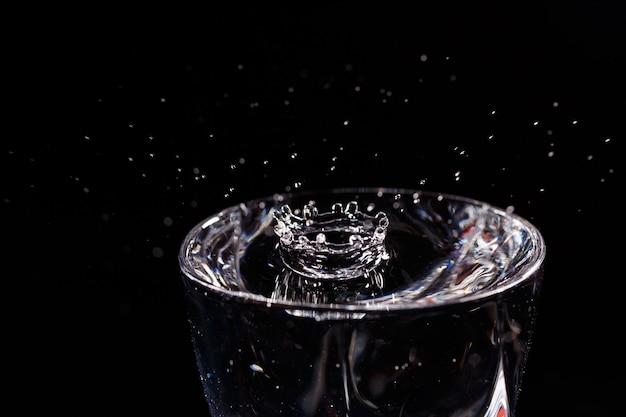 Czarne tło to szklanka, do której wpada kropla wody. rozpryskiwanie wody na szkle
