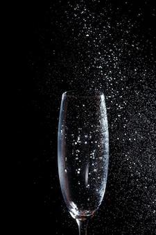Czarne tło to zbliżenie na czystą szklankę w jego dłoni. spryskaj szklankę wody. szkło izolacyjne