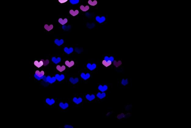 Czarne tło z niebieskimi fioletowymi sercami.