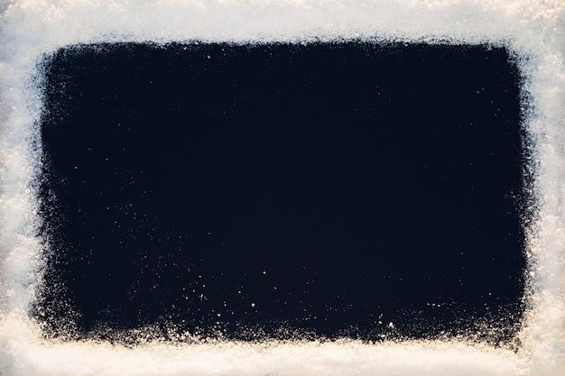Czarne tło z ramą tekstury śniegu w słońcu.