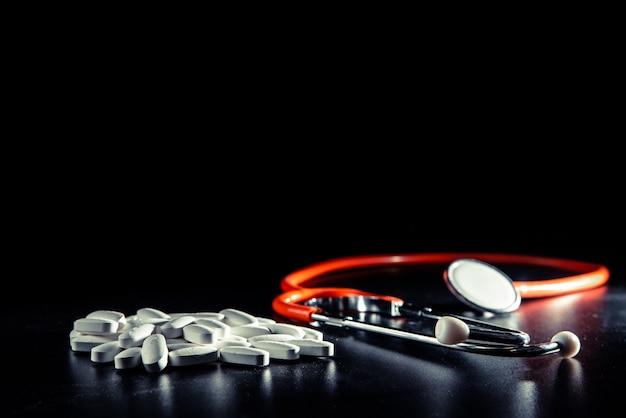 Czarne tło z stetoskopem, zdrowe odżywianie pozwala uniknąć przyjmowania leków.