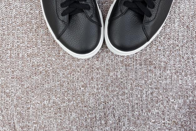 Czarne trampki na wełnianym tle. leżał płasko, widok z góry. koncepcja blogu mody. skopiuj miejsce na tekst