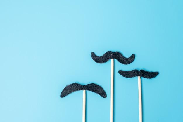 Czarne wąsy na niebieskim tle. szczęśliwego dnia ojca i międzynarodowego dnia mężczyzn