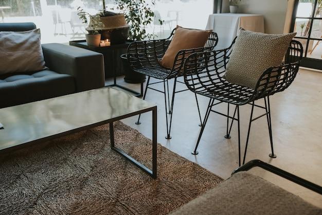 Czarne wiklinowe krzesła z poduszkami