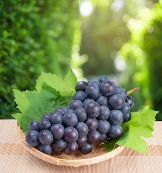 Czarne wino winogronowe z liśćmi w bambusowym koszu na drewnianym stole w ogrodzie, winogrono kyoho z liśćmi w rozmycie tła.