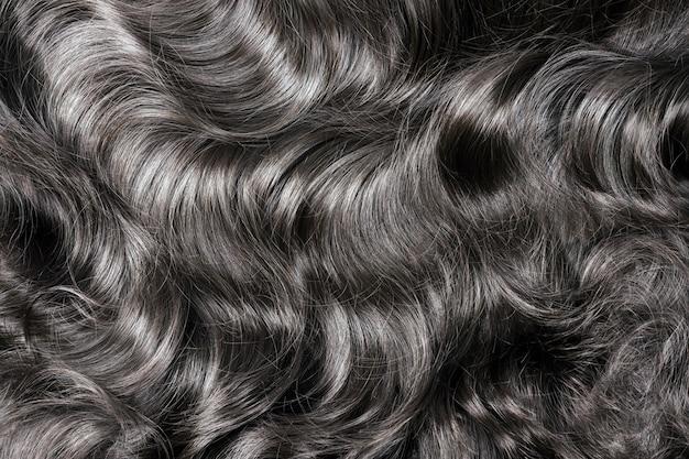 Czarne włosy tekstury. faliste długie kręcone ciemne włosy z bliska jako tło. przedłużanie włosów, materiały i kosmetyki, pielęgnacja włosów. fryzura, fryzura lub umieranie w salonie.