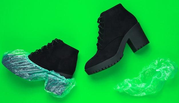 Czarne zamszowe botki z pokrowcami na buty na zielonym tle. widok z góry