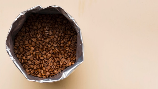 Czarne ziarna kawy na beżowym tle z miejsca na kopię