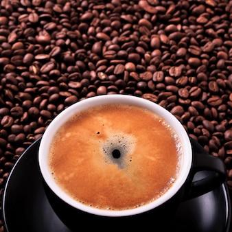 Czarnej filiżanki kawy espresso zbliżenia gorące fasole