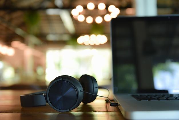 Czarni hełmofony i laptop na drewnianym stole na plamy sklep z kawą. motyw tworzenia muzyki cyfrowej.