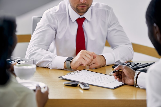 Czarni klienci podpisują umowę siedząc przy stole ze sprzedawcą