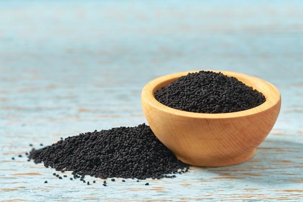 Czarni kminkowi ziarna w drewnianym pucharze na nieociosanym tle, selekcyjna ostrość.