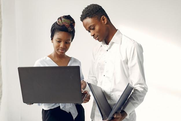 Czarni ludzie stojący na białej ścianie z laptopem